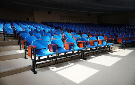 An auditorium with hundreds of empty bright blue seats