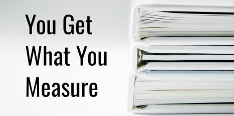 "The words ""you get what you measure"" next to a stack of white binders filled with papers"
