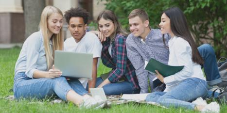 Group of business students sitting on the grass discussing project