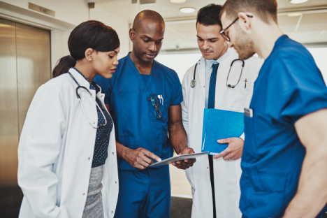 Group of four medical professionals discussing a file