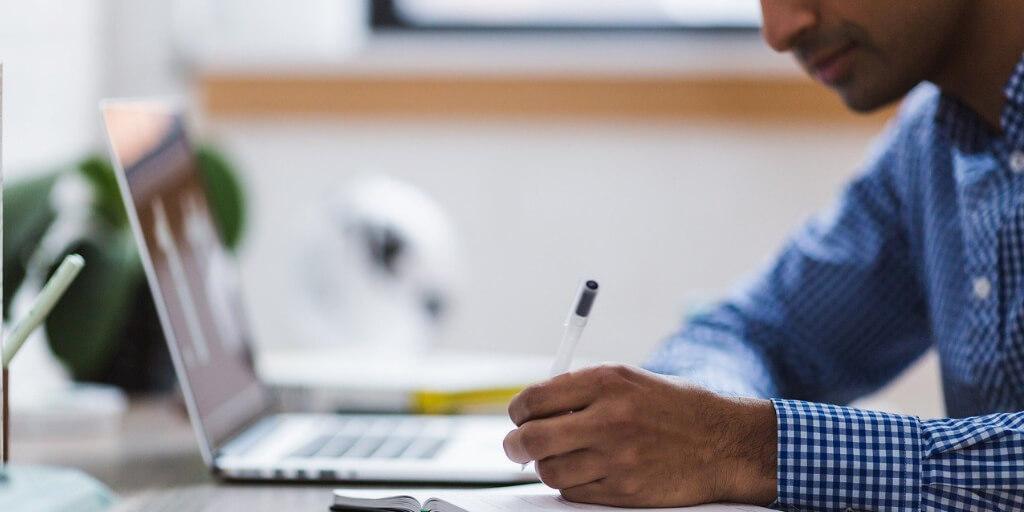Man working on laptop making notes