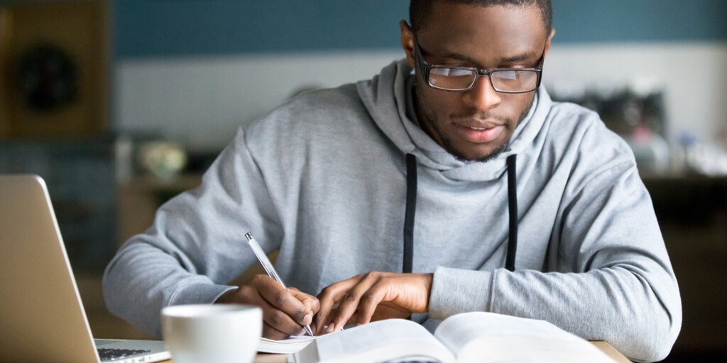 Higher Ed student sitting at desk focused on his tudying