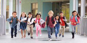 Enthusiastic students running down school hallway