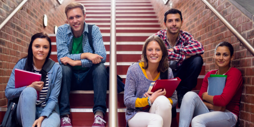 5 smiling college students sitting on a staircase at school