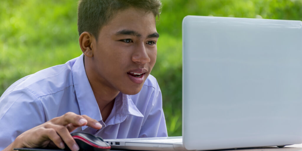 student working outdoors on his laptop