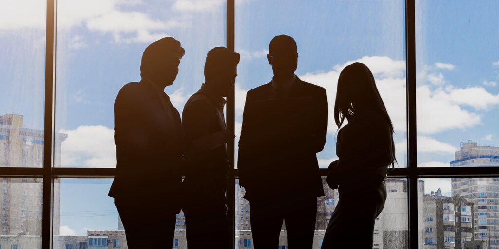 Group of job candidates, silhouetted against a window overlooking a city