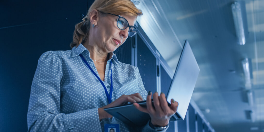 Business woman looking at laptop, evaluating data