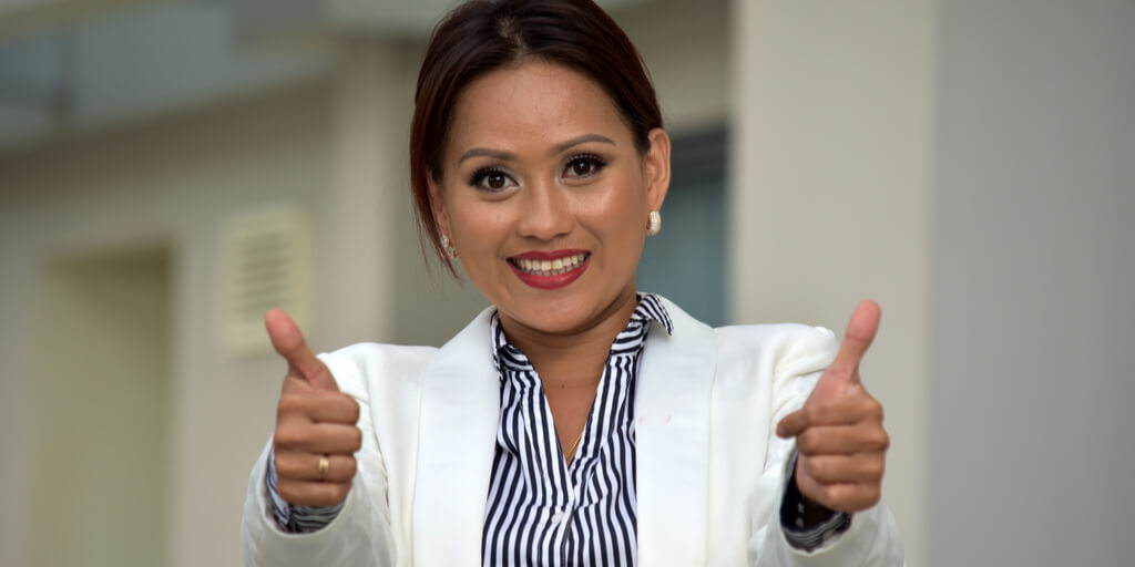 Smiling Business woman shows two thumbs up