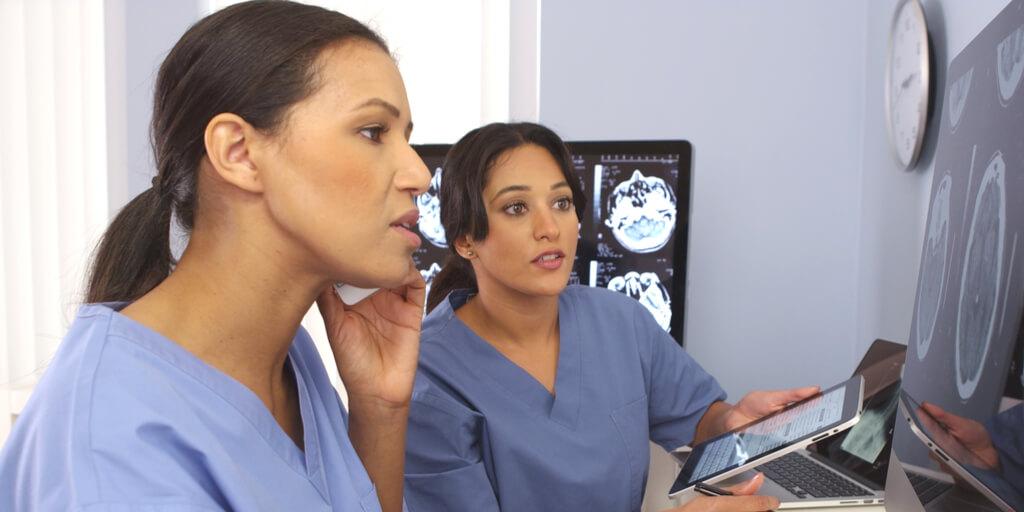 Two healthcare professionals confer about patient diagnosis