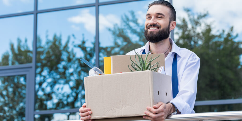 Happy employee carrying a box
