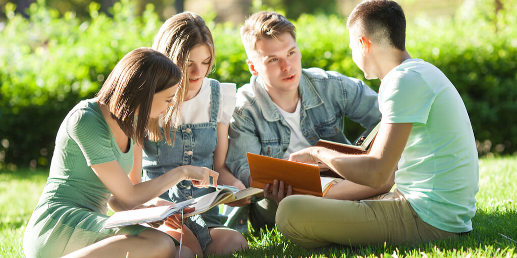 Group of four students sitting outside studying