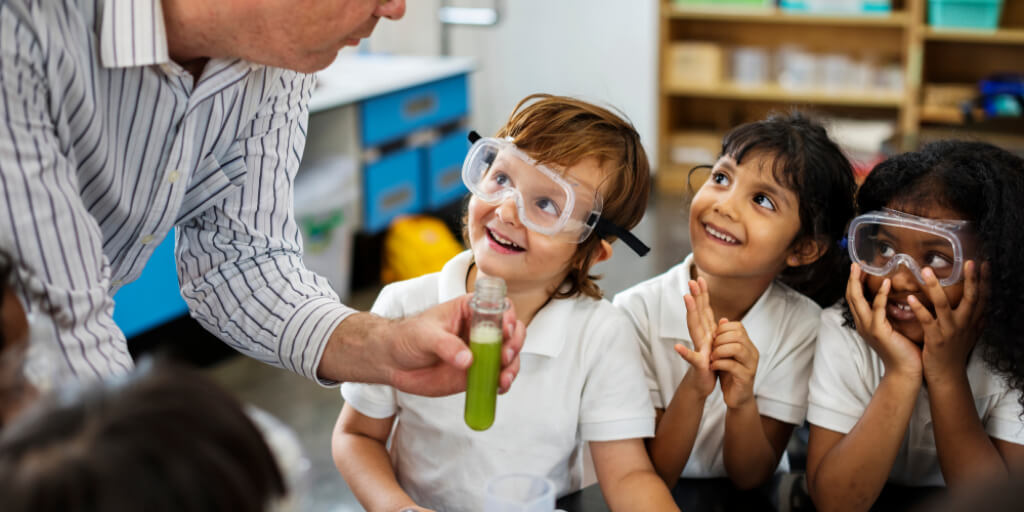 3 childrenwearing safety glasses smiling at man holding a test tube  filled with green liquid