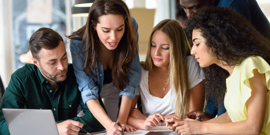 Group of 5 college students studying information in a report