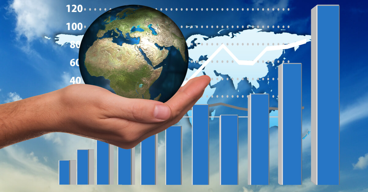Hand holding shiny globe in front of a histogram showing growth