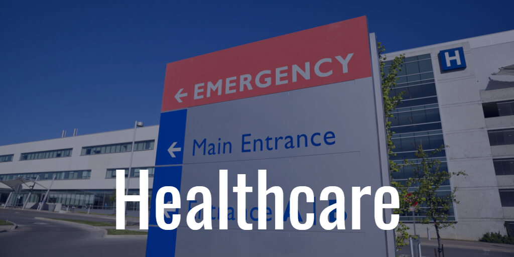 The word Healthcare labels a picture of a sign pointing way to the Emergency entrance of a hospital