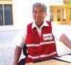 Smiling cashier wearing security vest
