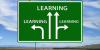 Long straight road approaching a green highway sign that shows four arrows,  each labelled Learning