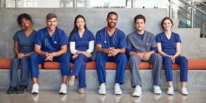 Row of smiling medical staff sitting on a bench in health care facility