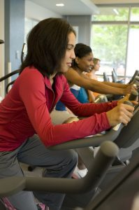 Woman in red blouse working out on exercise equipment