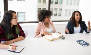 three women sitting at an office conference table in business discussion