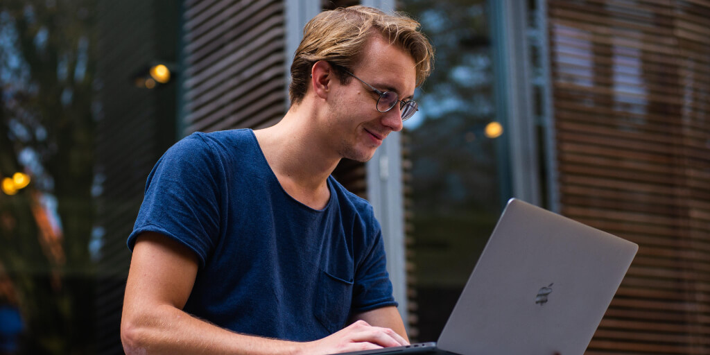 College student sitting in his backyard, doing virtual learning on his laptop