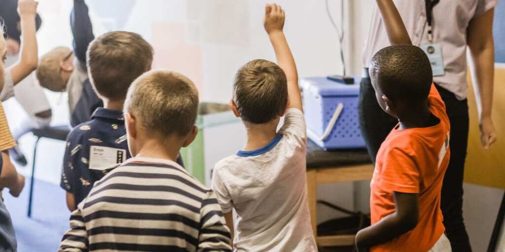 Young students raising hands to answer a question