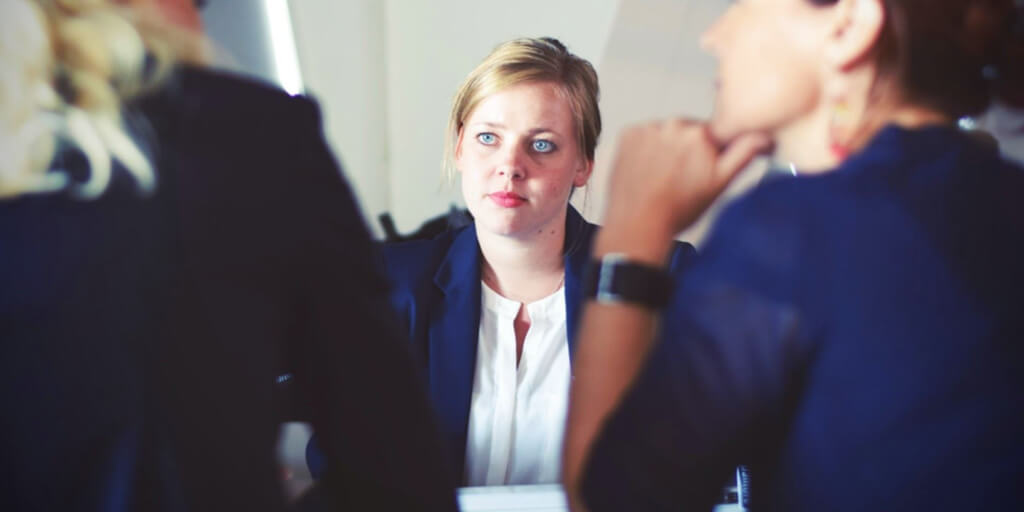 young woman looking across table at two people