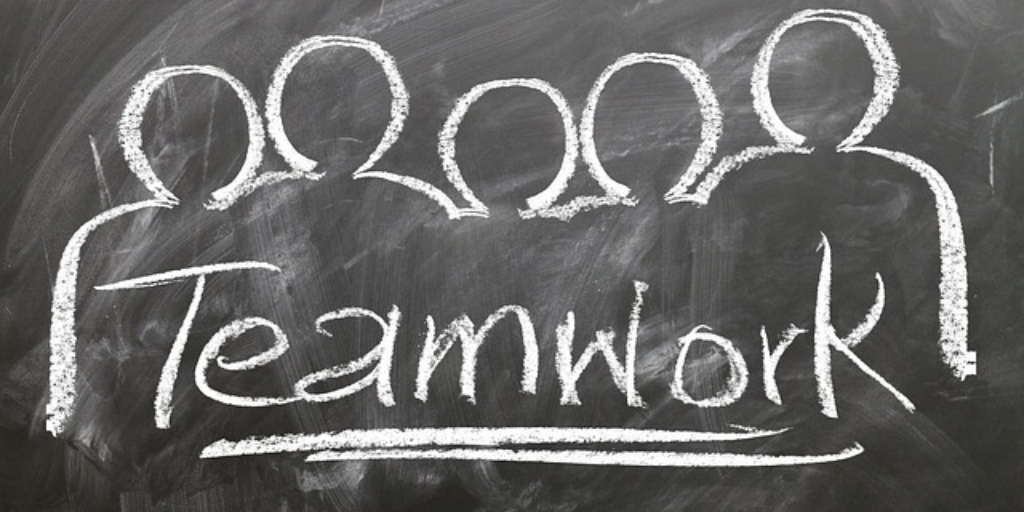 Chalkboard showing the word Teamwork surrounded by silhouettes of people