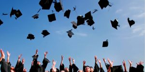 College graduation. Higher Education students celebrate by throwing mortarboards; critical thinking predicts success